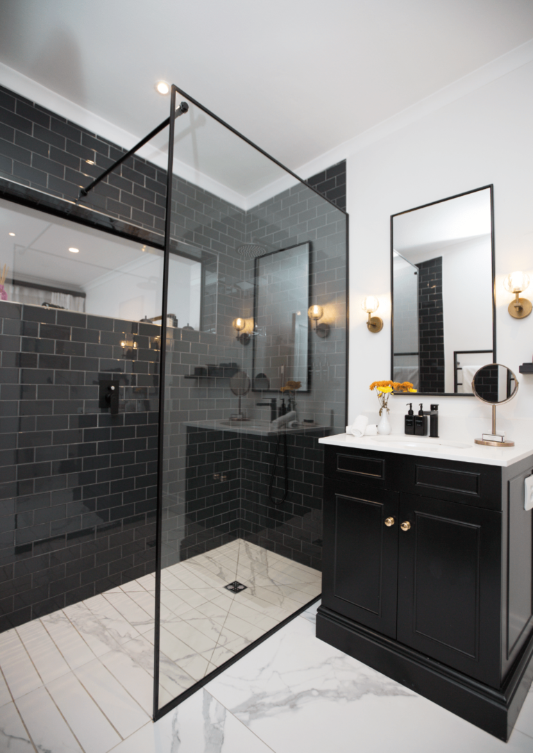 Walk-in rain shower with black tiles and sink in Manor room bedroom suite at Villa Coloniale