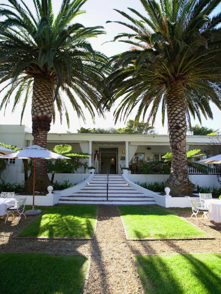 Outside Entrance with palm trees and al fresco seating at Villa Coloniale