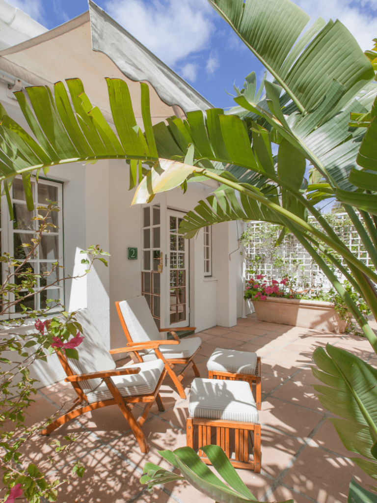 Two lounge chairs with footrests on patio with shade with view of garden at Villa Coloniale