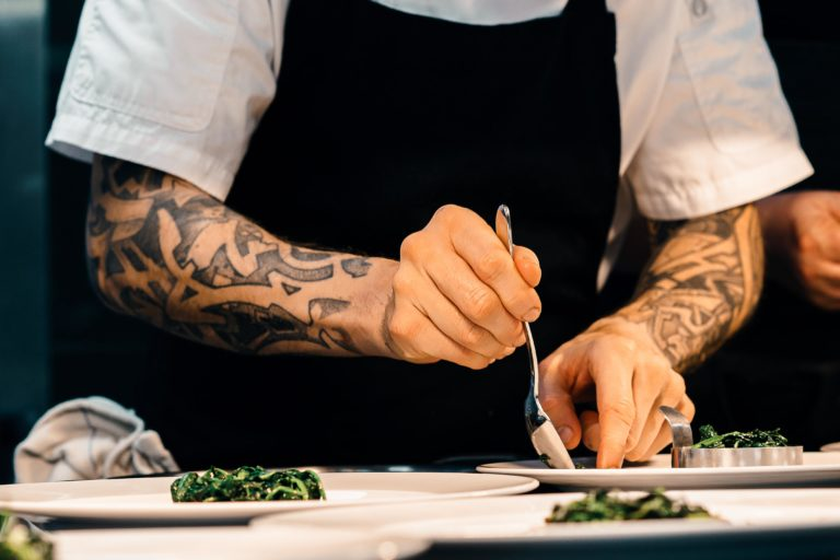 Tattooed chef plating food in fine-dining restaurant
