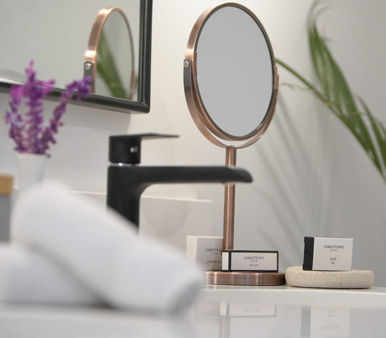 Beauty mirror, fresh towels and Charlotte Rhys soap in bathroom in Manor room bedroom suite at Villa Coloniale