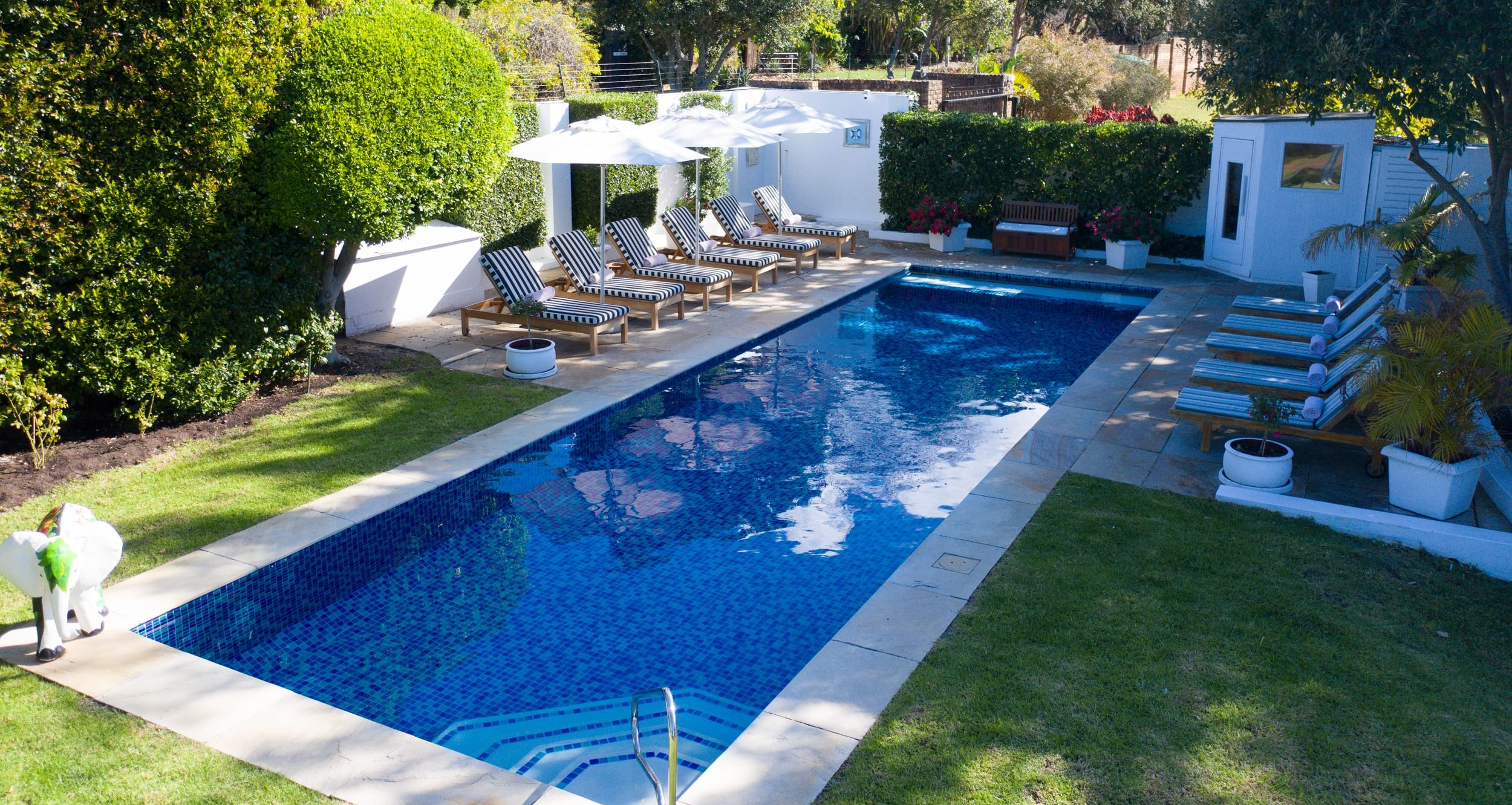 Shady swimming pool with umbrellas and black and white cushioned pool loungers