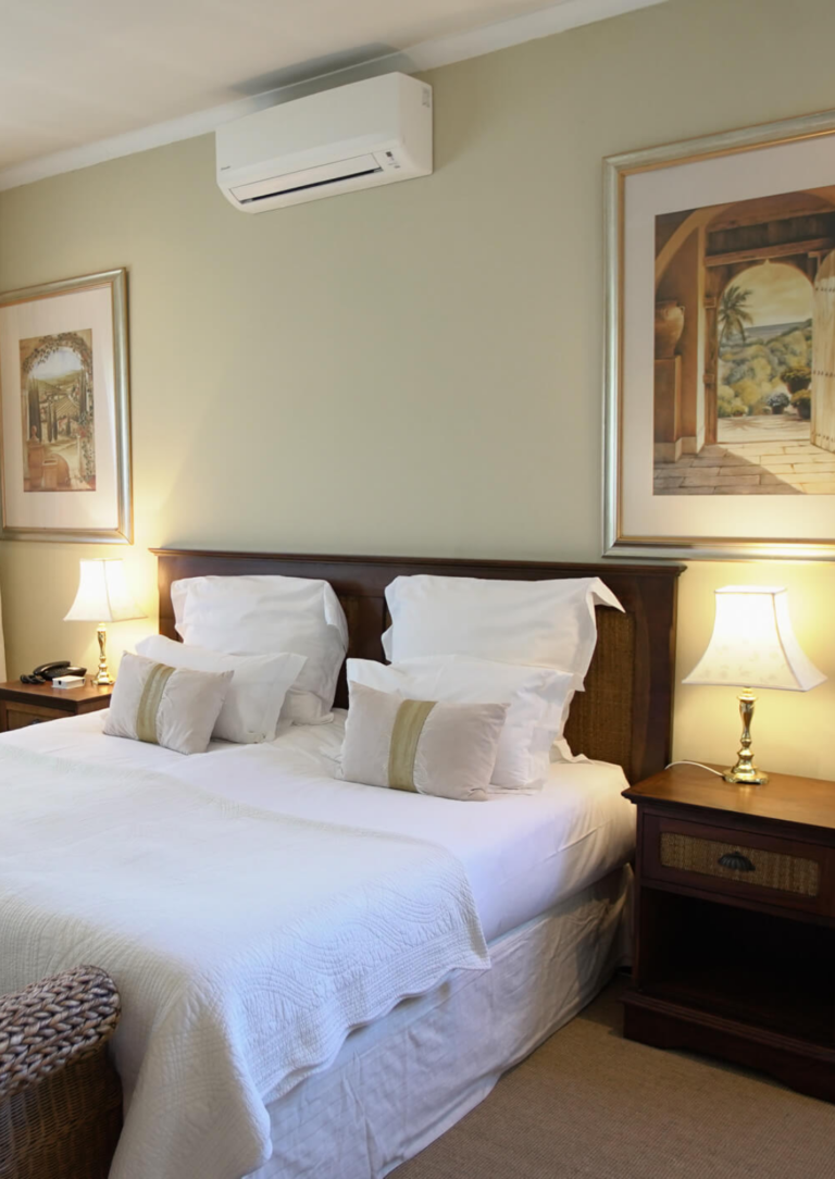 White bed with two pictures on the wall and aircon in the Deluxe Bedroom suite at Villa Coloniale