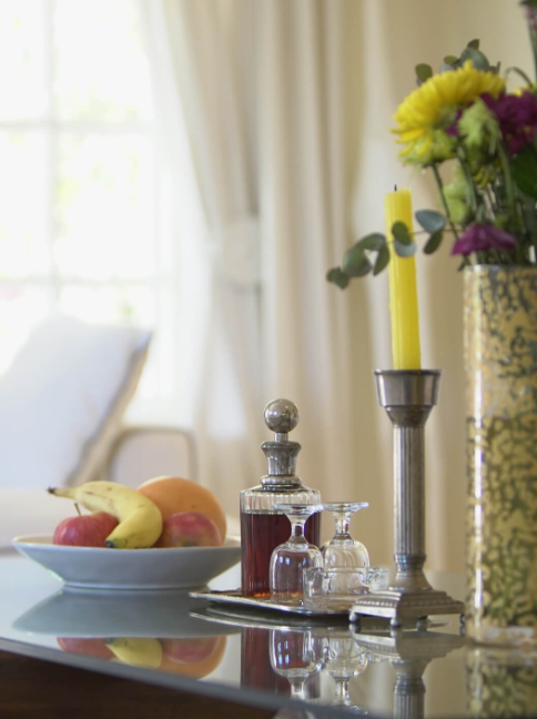 Fruit bowl, candlestick, flowers and sherry on table in lounge area at Villa Coloniale