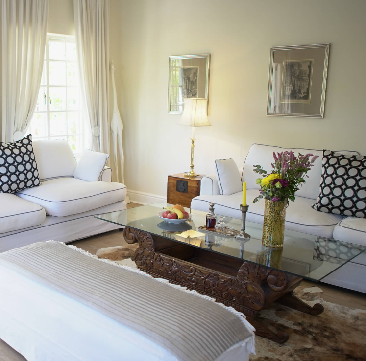 Glass table with flowers and couches in the Deluxe Bedroom suite at Villa Coloniale